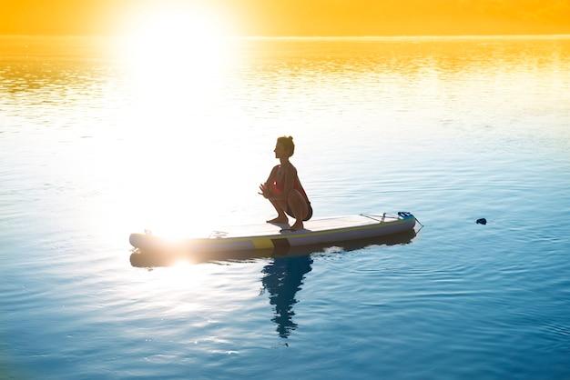 Женщина медитирует во время восхода солнца на доске с веслом