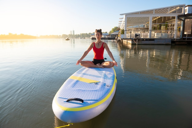 Woman meditating during sunrise on a paddleboard