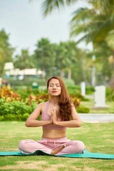 Woman meditating on green meadow