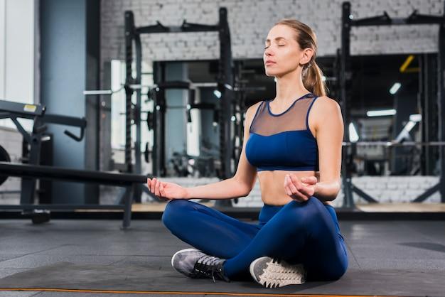 Woman meditating in gym