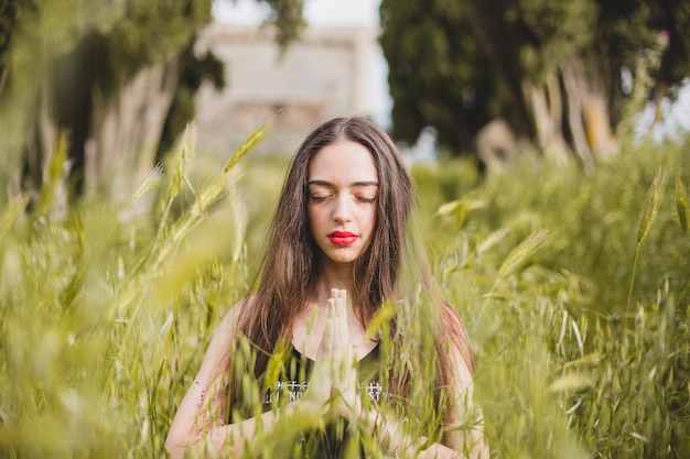 Woman meditating in high grass