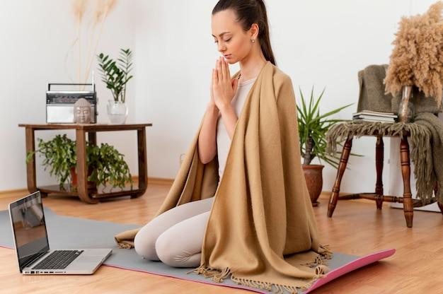 Donna che medita a casa sulla stuoia