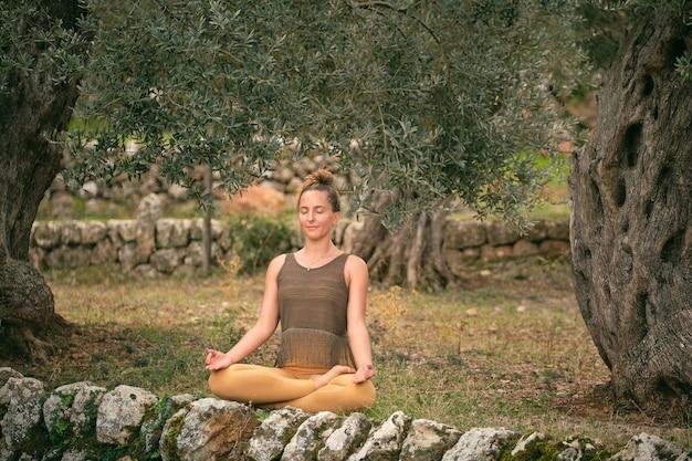 公園で蓮華座で瞑想する女性