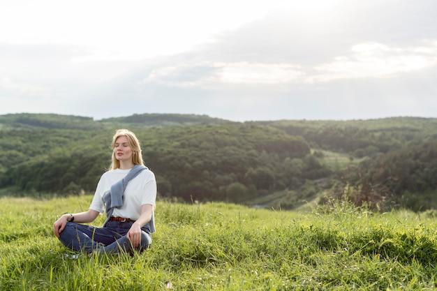 Женщина медитирует на природе