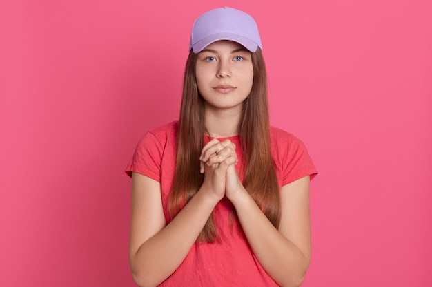 Woman meditating joining both her palms, looks at camera, wearing casual t shirt and baseball cap