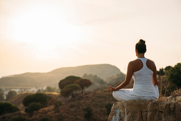 Woman meditating in the mountainside