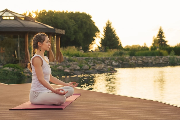 Woman meditating near lake at sunset time