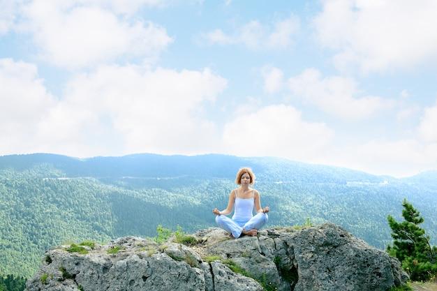 山を背景に瞑想する女性