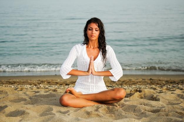 Женщина медитации на пляже