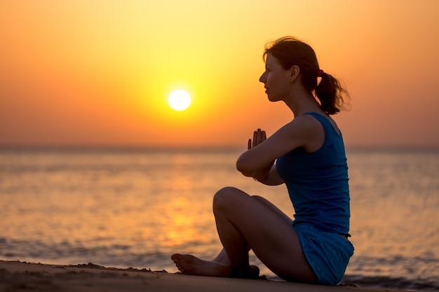 Женщина медитации на берегу моря