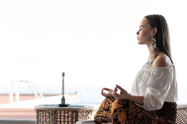 Женщина медитирует на открытом воздухе