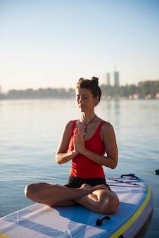 Woman meditating and practising yoga during sunrise on a paddleboard