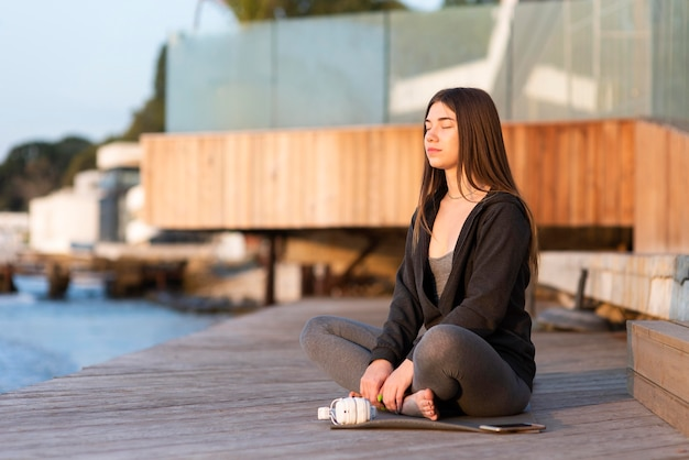 Woman meditating next to the sea