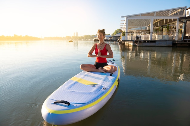 Woman meditating in a seiza position during sunrise in paddle board