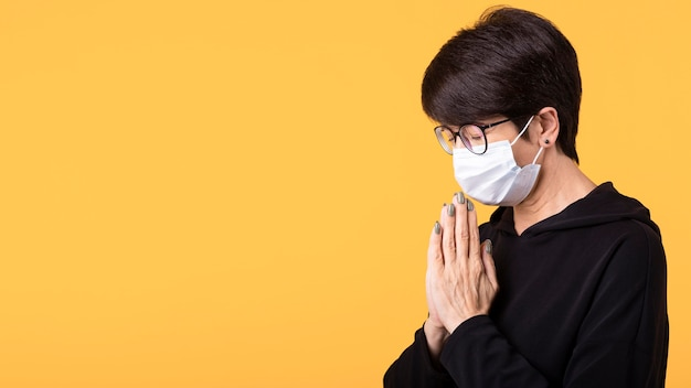 Woman meditating while wearing a medical mask with copy space