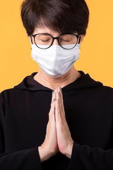Женщина медитирует с маской для лица на