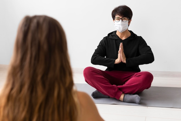 Woman meditating with a face mask on