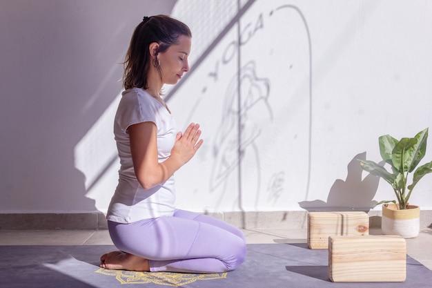 Женщина медитирует руками в позе анджали мудры в мирной обстановке