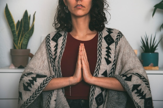 Woman meditating with the palms of the hand joined on the chest dressed with a handmade poncho