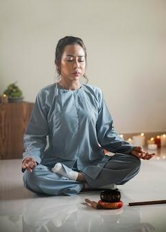 Женщина медитирует с поющей чашей и ладаном
