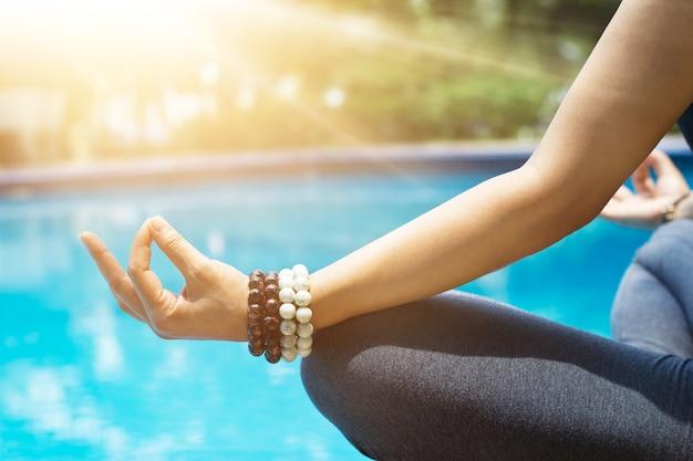 Женщина, медитируя с бисером запястья в положении лотоса йога в синем бассейне