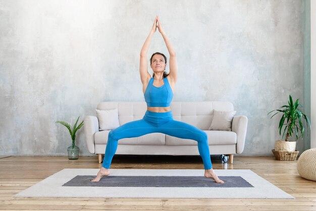 Женщина медитирует йогой, стоя дома на коврике