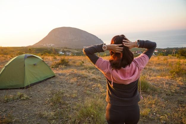 女性は山で夜明けに出会い、太陽の下で喜びます。山と海を上から見たパノラマビュー。キャンプ、野外活動、スポーツ山岳ハイキング、家族旅行。アユダグ、クリミア。