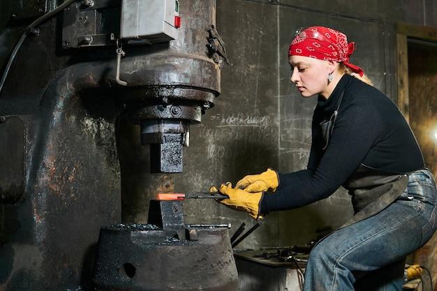 Художница по металлу обрабатывает горячую деталь с помощью молотка в мастерской
