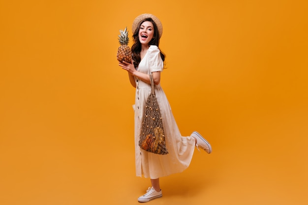 Woman in midi dress, hat and sneakers holds shopping bag and pineapple on orange background.
