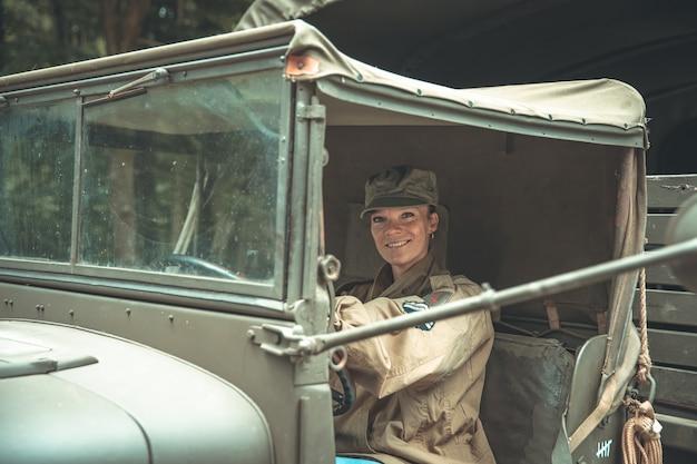 Woman in a military uniform in an army car.