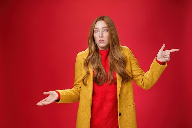 女性は、クライアントが混乱してポーズをとるのを見逃し、肩をすくめることがどのように起こったのかを知らずに、手のひらを右に向けて、赤い背景の上のカメラを疑って不確かに見ている無知なジェスチャーをしました。