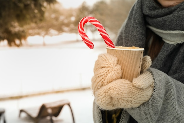 Woman in mittens hold cup of hot drink outdoor in winter