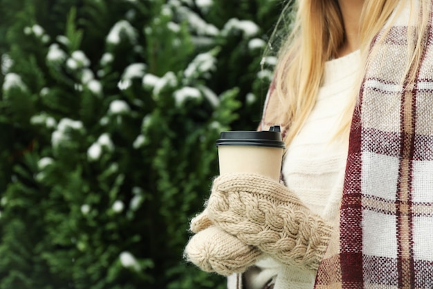 Woman in mittens and plaid holding coffee outdoor
