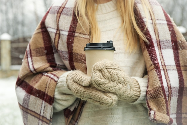 Woman in mittens and plaid holding coffee in snowy weather