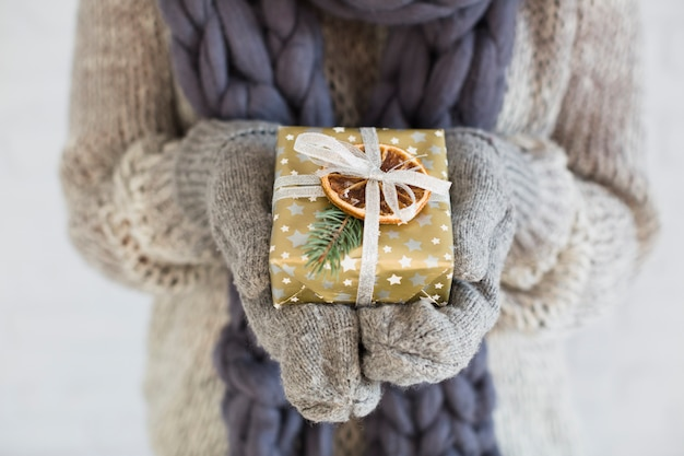 Woman in mitts and scarf with present box in hands