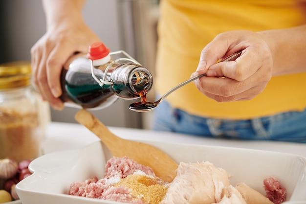 Женщина смешивает фарш с соевым соусом