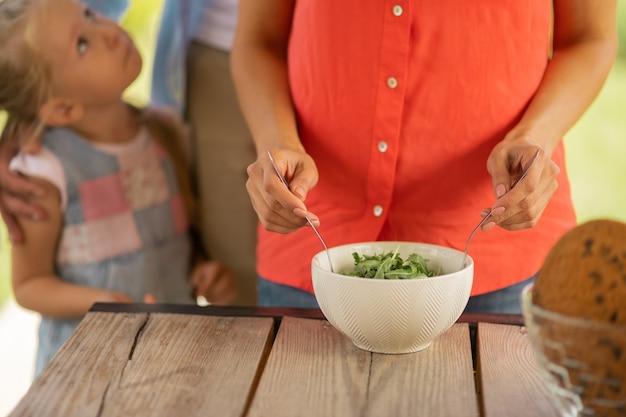 サラダを混ぜる女性。娘と夫の近くに立って外で昼食を調理しながらサラダを混ぜる女性のクローズアップ