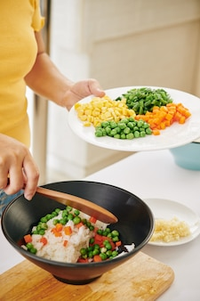 Woman mixing vegetables with rice