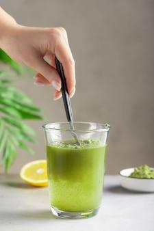 緑のスーパーフードパウダーと水を混ぜる女性