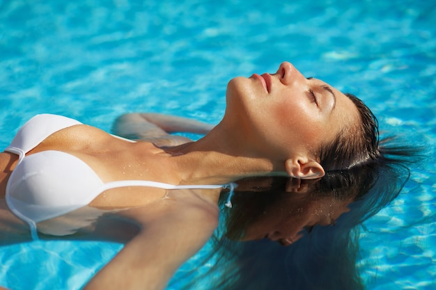 Woman model in bikini is relaxing in swimming pool