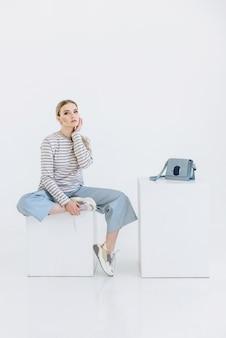 Блондинка женщина модель сидит на кубе на белой сцене