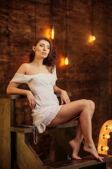 Брюнетка женщина модель красивое и модное короткое белое платье сидит на деревянной лестнице в студии, на заднем плане