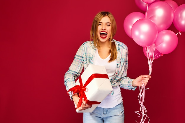 Woman model celebrating and holding box with gift present and pink air balloons