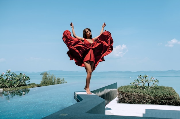 Woman model in fashion red dress standing  on the  edge of infinity swimming pool with sea view.