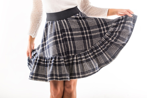 Woman model holds in her hands her beautiful plaid skirt posing in the studio on white
