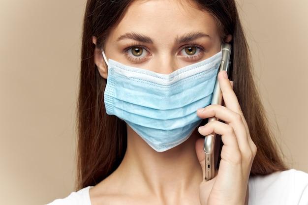 医療マスクの女性モデルは楽しみにして、ベージュ色の背景に彼女の手で携帯電話を保持しています。