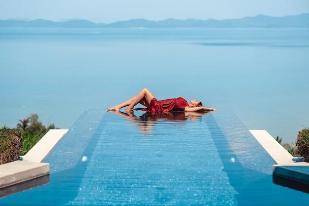 海の景色を望むインフィニティプールの端に横たわるファッション水着の女性モデル