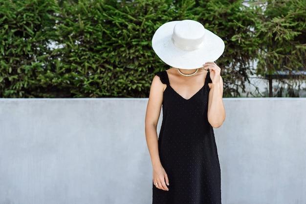 새 옷 카탈로그에서 도시 거리의 배경에 포즈를 취하는 모자와 검은 드레스를 입은 여성 모델
