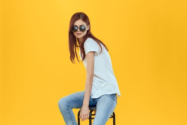 Модель женщины в джинсах и белой футболке позирует на цветном пространстве