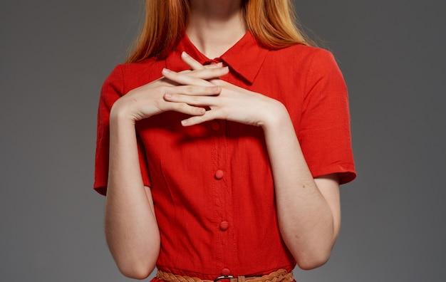 コピースペースでトリミングされた孤立した壁に赤いドレスの女性モデル。